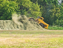 The fertilizer. The wheeled tractor, levels a heap of fertilizer on a field stock image
