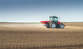 Fertilizer agriculture. Tractor and fertilizer spreader in field royalty free stock photography
