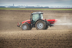 Fertilizer agriculture. Tractor and fertilizer spreader in field Royalty Free Stock Images