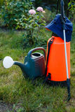 Fertilizer pesticide garden sprayer and watering can on green gr Stock Photo