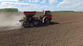 Fertilizer spreader. The fertilizer spreader moves across the field and spreads dry fertilizers. The camera flies over the car stock video footage