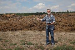 Fertilizzante naturale, sterco di mucca nel campo e agricoltore o agronomo Fotografia Stock