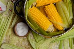 Fervura do milho doce com sal milho doce cozinhado no potenciômetro na tabela de madeira Fotografia de Stock