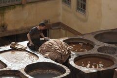 FES, MARRUECOS - 20 DE FEBRERO DE 2017: Sirva el trabajo dentro de los agujeros de la pintura en la curtiduría famosa de Chouara  Imagen de archivo libre de regalías