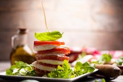 Fesh Italian Caprese. Salad with sliced mozzarella and herbs royalty free stock photo