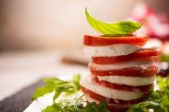 Fesh Italian Caprese. Salad with sliced mozzarella and herbs stock photo