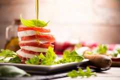 Fesh Italian Caprese. Salad with sliced mozzarella and herbs stock photography