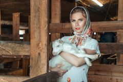 Feshion woman on the farm holding a little goat in her arms royalty free stock photos