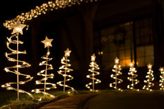 Fesitve Lights. Fesitve outdoor holiday lights in the shape of Christmas trees, topped with lit stars. Image is set outside a domestic house at night time stock photo