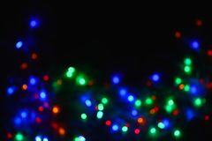 Festão colorida das luzes na obscuridade Iluminação festiva do efeito de Bokeh imagens de stock royalty free