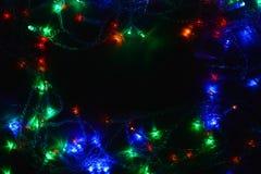 Festão colorida das luzes na obscuridade Iluminação festiva do efeito de Bokeh foto de stock royalty free