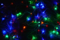 Festão colorida das luzes na obscuridade Iluminação festiva do efeito de Bokeh fotografia de stock royalty free