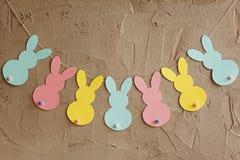 Festão com coelhos de papel coloridos no fundo cinzento Conceito de Easter Foto de Stock