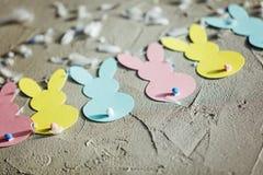 Festão com coelhos de papel coloridos no fundo concreto Páscoa Bunny Banner do conceito Vista superior Fotos de Stock Royalty Free