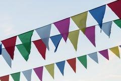 Festão das bandeiras coloridas da forma triangular, flâmulas contra o céu azul Feriado da rua da cidade Fundo moderno, bandeira Fotos de Stock