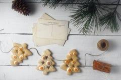 Festão de cookies e de cartão do Natal na opinião superior do fundo de madeira branco Fotos de Stock