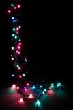 A festão decorativa romântica do Natal ilumina o quadro no fundo preto com espaço da cópia Fotos de Stock
