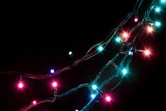 A festão decorativa romântica do Natal ilumina o quadro no fundo preto com espaço da cópia Foto de Stock Royalty Free