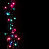 A festão decorativa romântica do Natal ilumina o quadro no fundo preto com espaço da cópia Fotografia de Stock Royalty Free