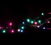 A festão decorativa romântica do Natal ilumina o quadro no fundo preto com espaço da cópia Imagem de Stock Royalty Free