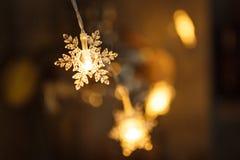 A festão do feriado, floco de neve plástico claro incandesce com uma luz dourada fotografia de stock