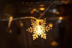 A festão do feriado, floco de neve plástico claro incandesce com uma luz dourada foto de stock