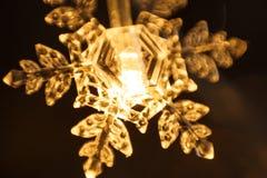 A festão do feriado, floco de neve plástico claro incandesce com uma luz dourada fotos de stock