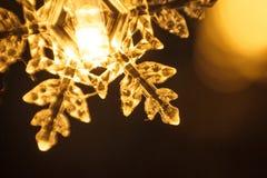 A festão do feriado, floco de neve plástico claro incandesce com uma luz dourada foto de stock royalty free