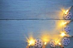A festão do Natal ilumina-se no fundo de madeira azul com espaço da cópia Imagens de Stock