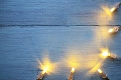 A festão do Natal ilumina-se no fundo de madeira azul com espaço da cópia Decoração do Natal fotografia de stock royalty free