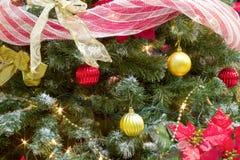 Festão e luzes vermelhas da árvore de Natal da quinquilharia do ouro imagem de stock