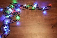 festão elétrica de Novo-ano em um fundo de madeira Bulbos brilhantes o Imagem de Stock