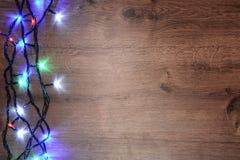 festão elétrica de Novo-ano em um fundo de madeira Bulbos brilhantes o Imagem de Stock Royalty Free