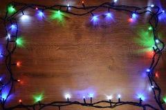 festão elétrica de Novo-ano em um fundo de madeira Bulbos brilhantes o Fotografia de Stock Royalty Free