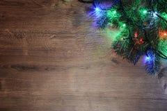 festão elétrica de Novo-ano em um fundo de madeira Bulbos brilhantes o Fotos de Stock Royalty Free