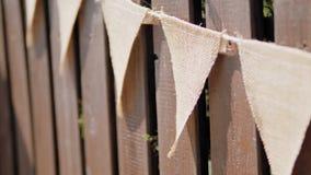 Festão festiva das bandeiras de linho do triângulo na cerca de madeira no dia de verão no feriado filme