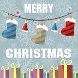 Festão festiva das botas, os chapéus e luzes coloridos e caixas com presentes em um fundo cinzento delicado com flocos de neve li Fotografia de Stock Royalty Free
