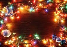 Festões do Natal das lâmpadas em um fundo de madeira Imagem de Stock Royalty Free