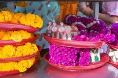 Festões florais e elefantes de madeira na bandeja vermelha para a venda no santuário de Erawan imagens de stock