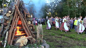 Fest von John-Parade und von großem Klotz stapelte brennendes Feuer in der Wiese stock footage
