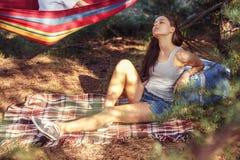 Festa, att campa av män och kvinnagruppen på skogen dem som kopplar av och äter grillfesten royaltyfri fotografi