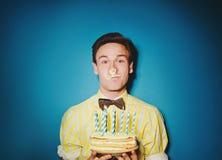 Festa beröm med den unga mannen med en kaka royaltyfria bilder
