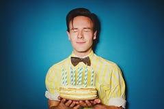 Festa beröm med den unga mannen med en kaka royaltyfri fotografi