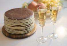 Festa con due vetri di champagne, del dolce e della frutta Fotografie Stock