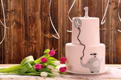 Festa de anos com o bolo de aniversário cor-de-rosa e elefante em um de madeira Imagens de Stock