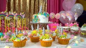 A festa de anos das crianças decoradas com queques saborosos, os pirulitos coloridos e o bolo do unicórnio vídeos de arquivo
