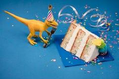 Festa de anos do dinossauro com fatia de bolo imagens de stock royalty free