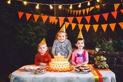 Festa de anos do ` s das crianças Três meninas alegres das crianças na tabela que comem o bolo com suas mãos e que mancham sua ca Fotografia de Stock Royalty Free