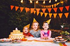 Festa de anos do ` s das crianças Três meninas alegres das crianças na tabela que comem o bolo com suas mãos e que mancham sua ca Imagens de Stock
