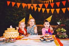 Festa de anos do ` s das crianças Três meninas alegres das crianças na tabela que comem o bolo com suas mãos e que mancham sua ca Imagens de Stock Royalty Free